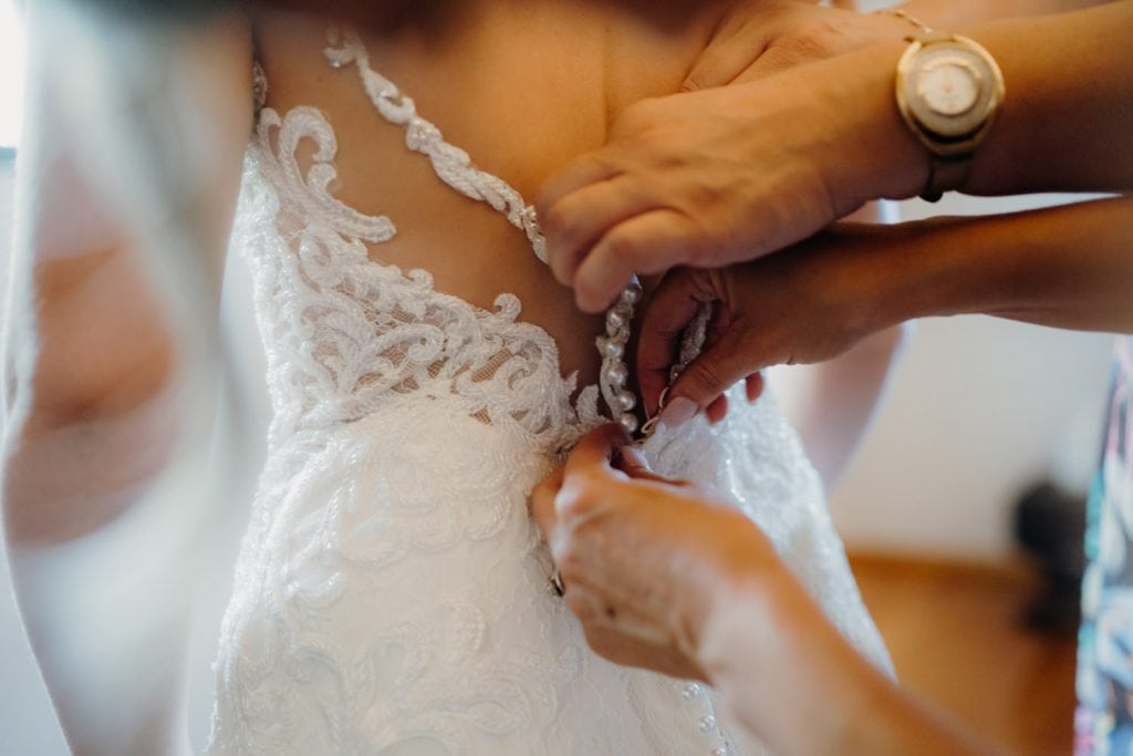 back of wedding dress with hands
