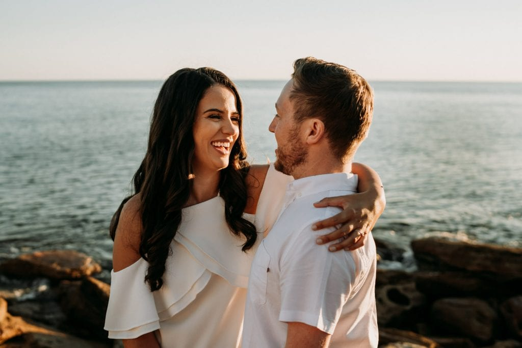 woman has her arm around her partner and smiles at him with ocean in the background at Gantheaume Point engagement session