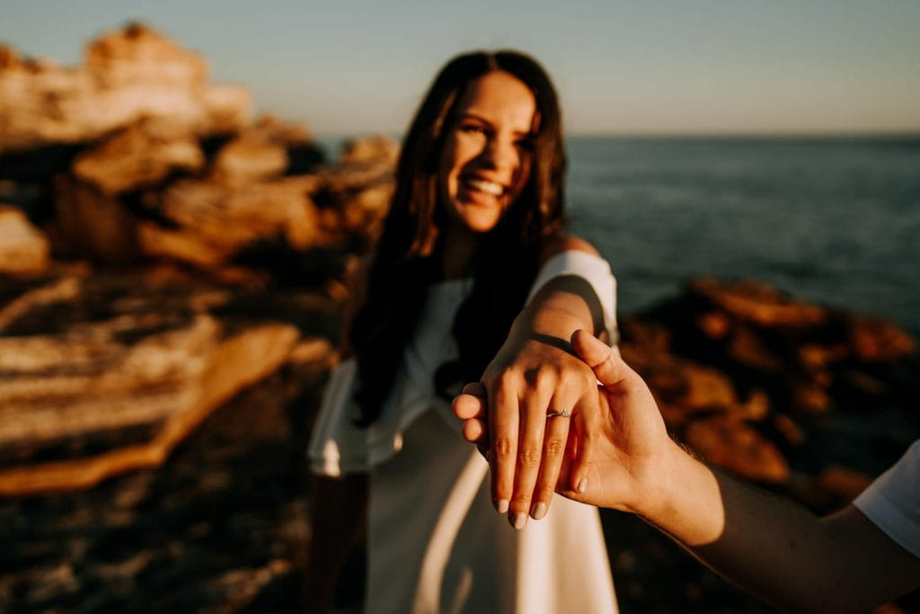 woman holds out her hand with engagement ring and man holds her hand