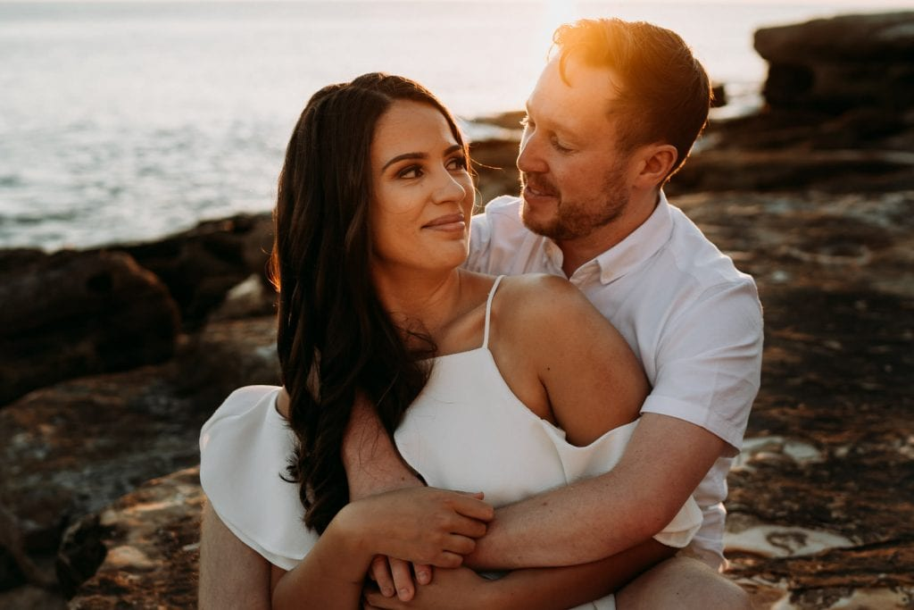 engaged young couple sitting on rocks at Gantheaume Point with warm sun light shining through and ocean behind them