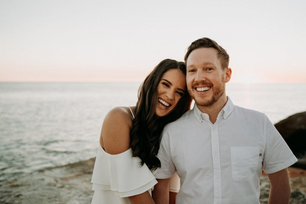 young couple smiling directly at the camera during engagement photos at Gantheaume Point