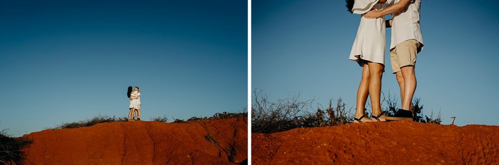 engaged couple standing on top of big red rock at Gantheaume Point in Broome