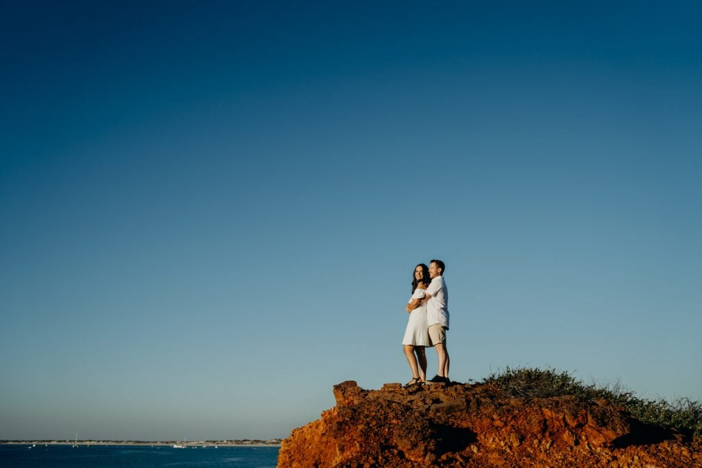 young man and his girlfriend standing close together at cliff edge at Gantheaume Point in Broome dduring Gantheaume Point engagement shoot