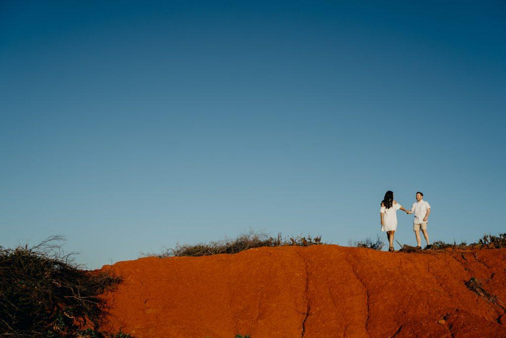 man and woman walking on big red rock looking a bit like Uluru