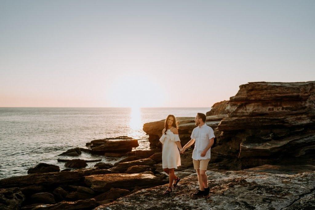 engaged couple walking along flat rocks during their Gantheaume Point engagement shoot