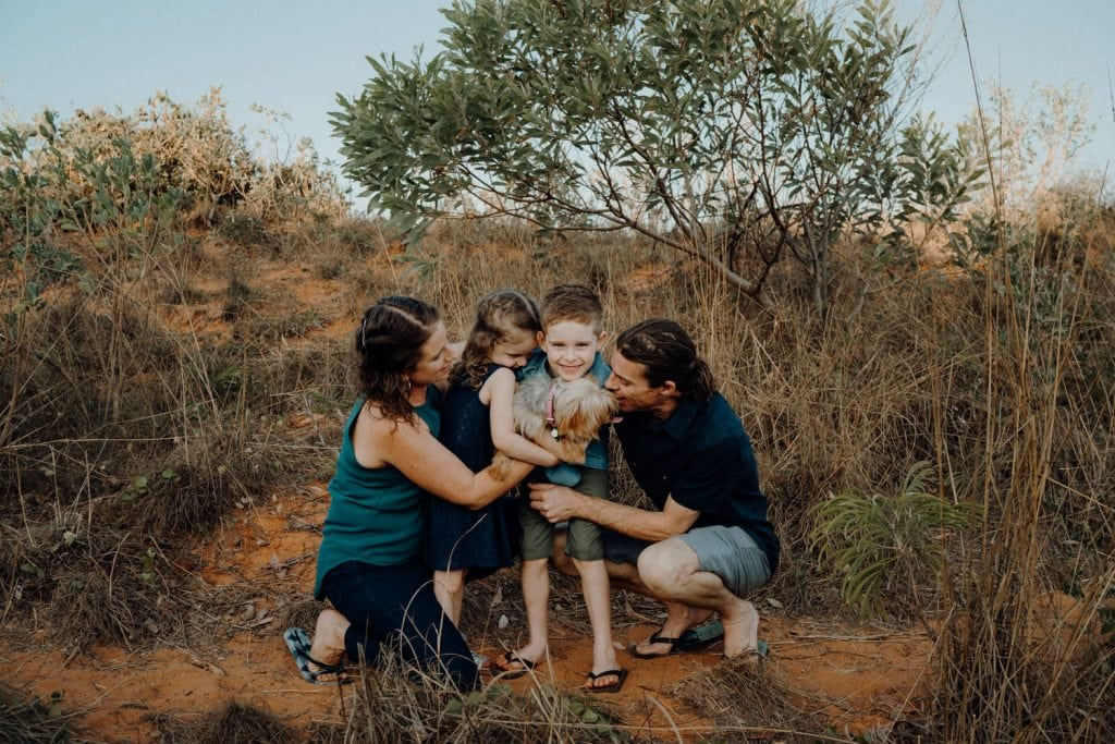 family of 4 with little dog hugging in bushland behind Reddell Beach dunes during family photo shoot with Julia Rau Photography