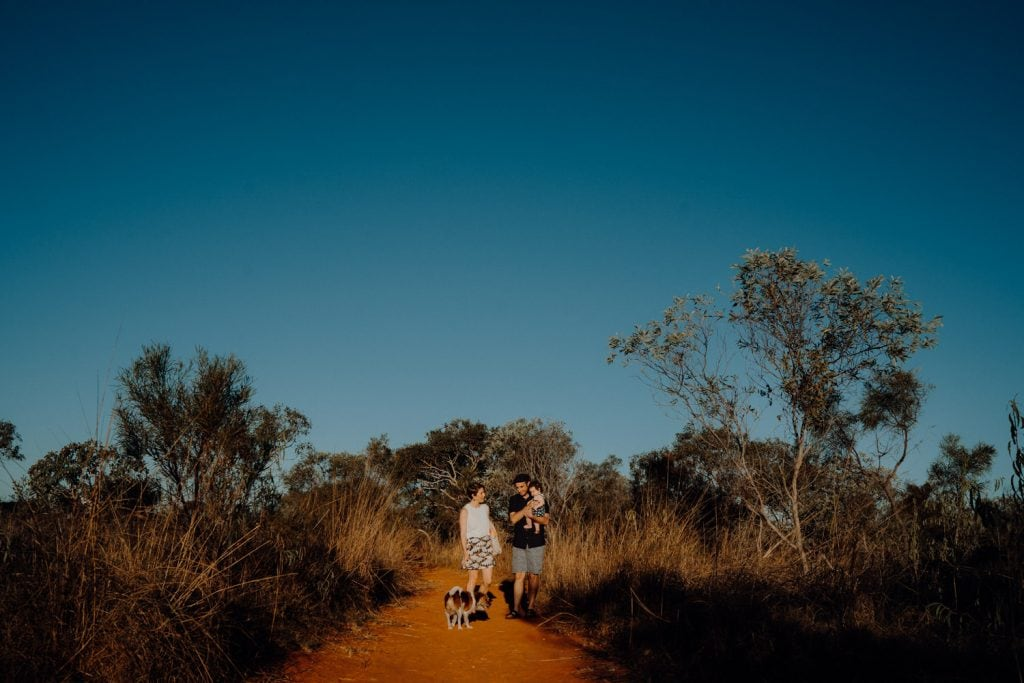 Family with baby and dog walking down a bush track as part of their Broome Family Photographer session