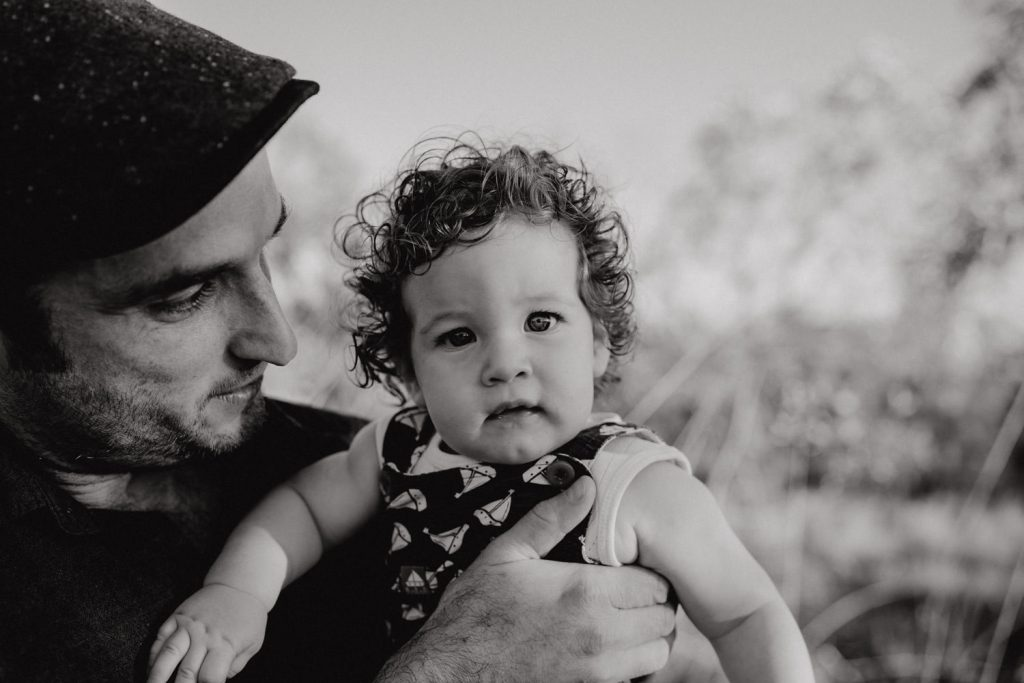 baby boy looks at the camera with dad holding him Broome Family Photographer