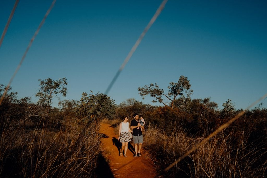young family with dog walk along a path in bushland in Broome