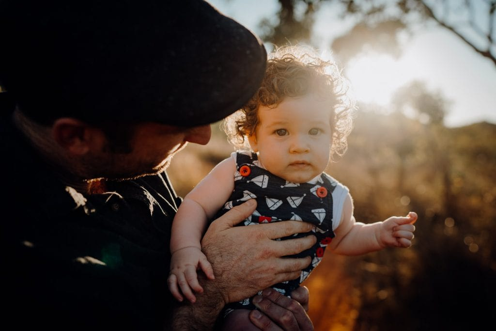 back lit close up of young baby boy in his father's arms during Broome Family Photographer Session