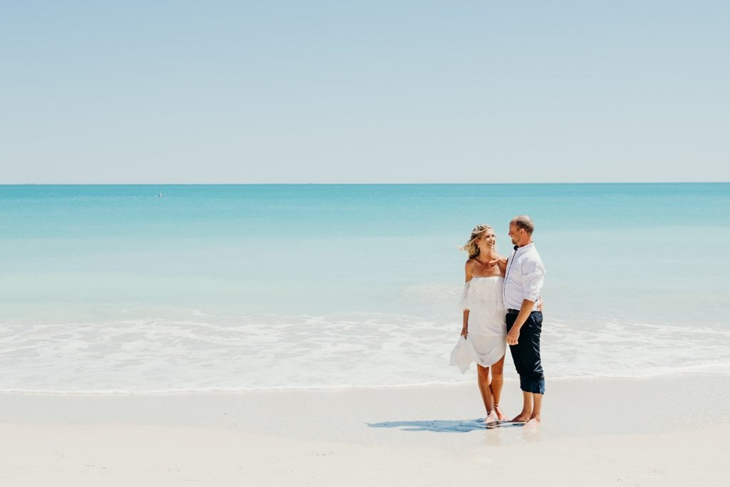 bride and groom getting married in Broome in the shallow water on Cable Beach with ocean in the background