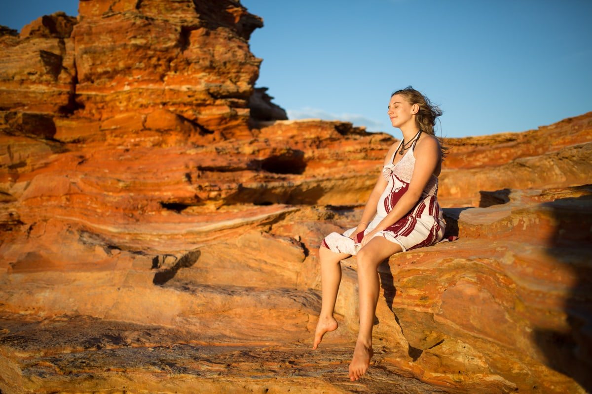 woman sits on red cliffs at Gantheaume Point Broome