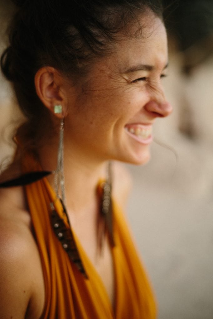 woman with long earings and big smile