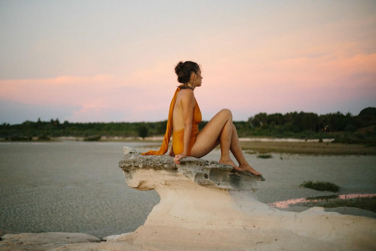beautiful woman sitting on rock formation