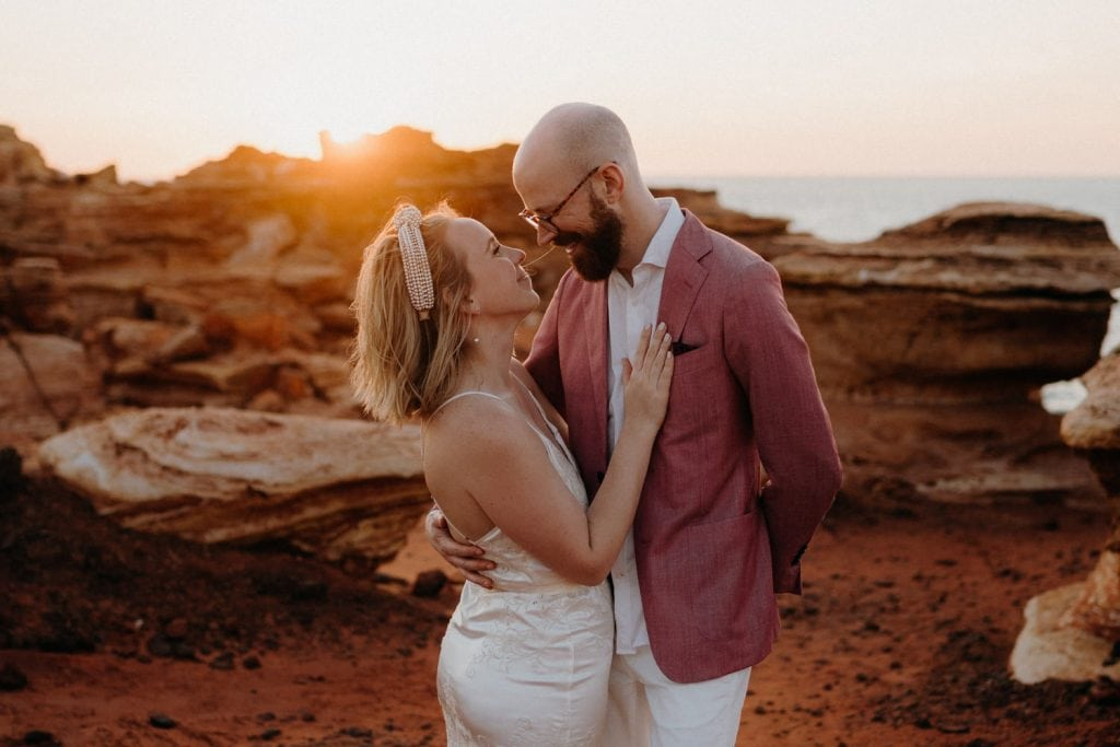 Broome elopement wedding couple at sunset in front of red rocks at Gantheaume Point