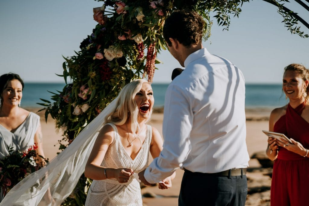 bride holds hands of groom during wedding ceremony in Broome and laughs