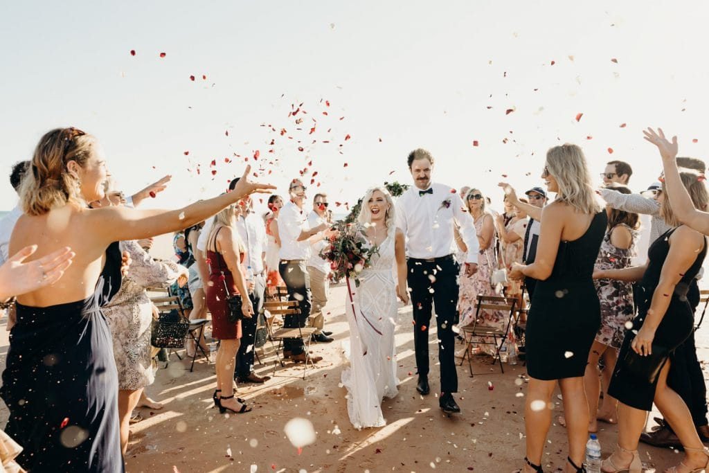 bride and groom walking down the sandy beach aisle at Entrance Point wedding with guests throwing flower petals