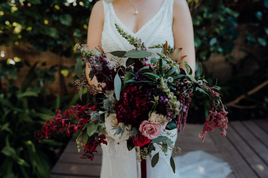 bride holds a beautiful large flower bouquet by Broome Florist