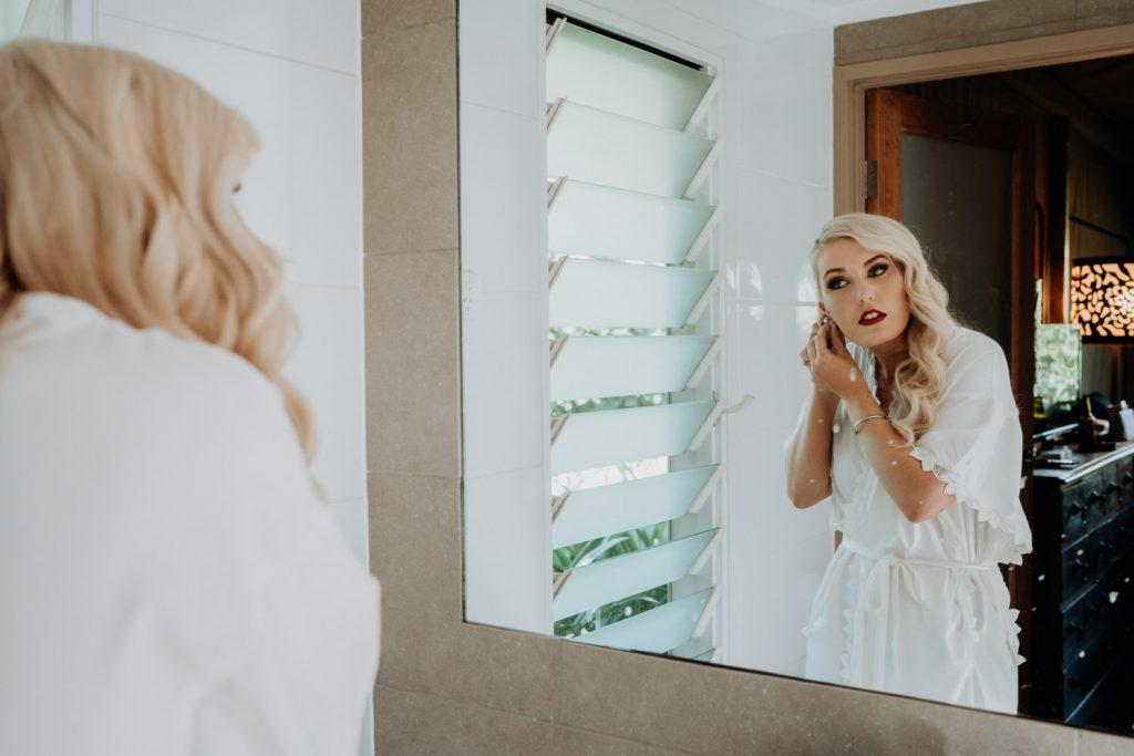 bride in white getting ready robe is putting in earnings in bathroom