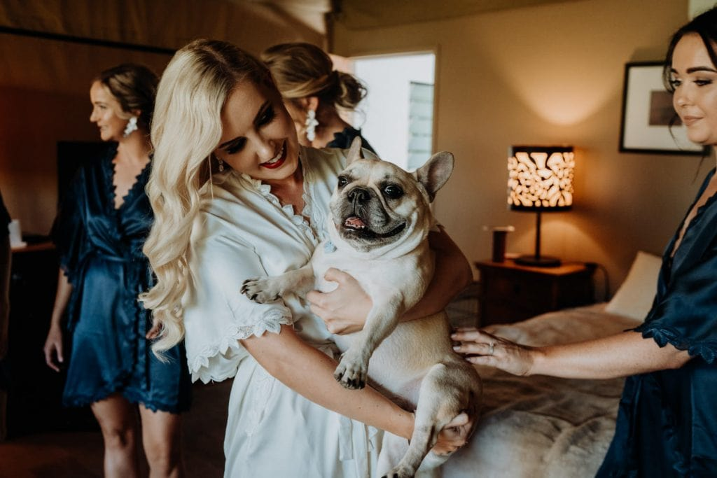 bride in getting ready robe is holding her dog in her arms