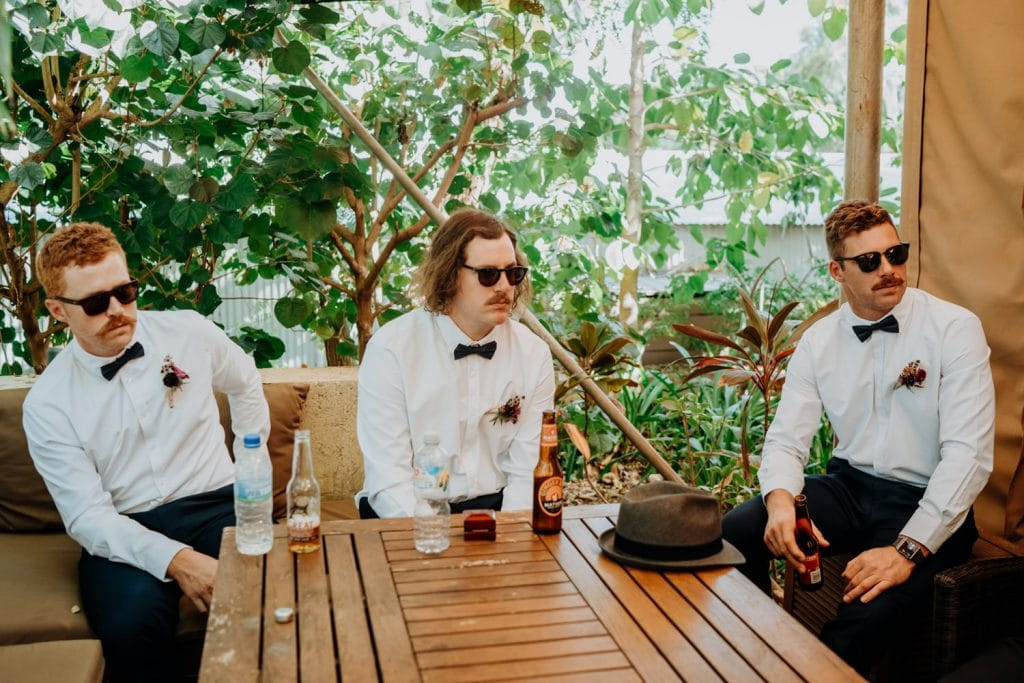 three young man with moustaches and white shirts and bow ties at billi resort in Broome