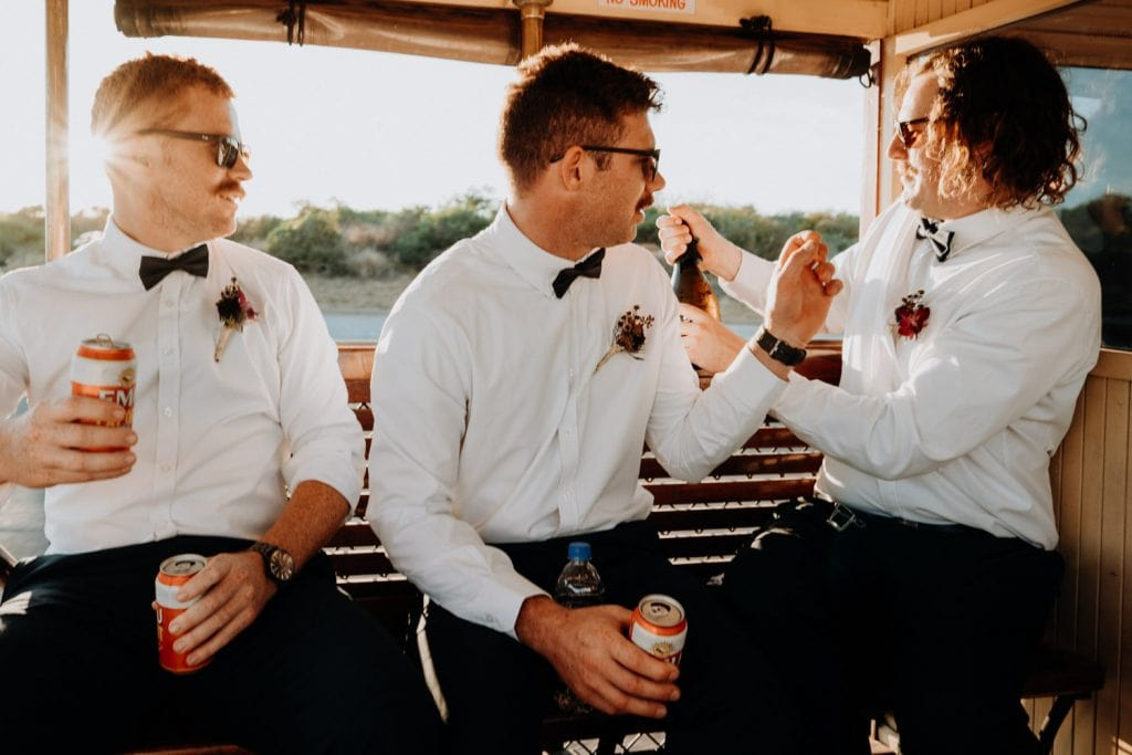 three young men sitting in Broome Tramway opening champagne and drinking cans of beer