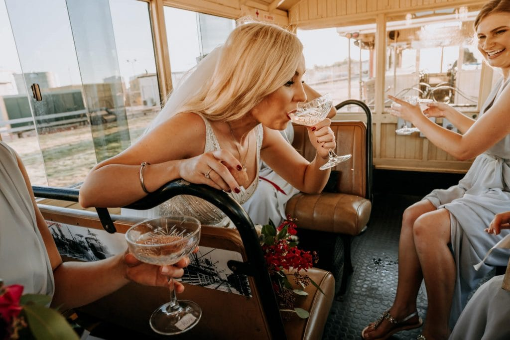 Broome Entrance Point wedding party travelling in Broome Tramway drinking champagne