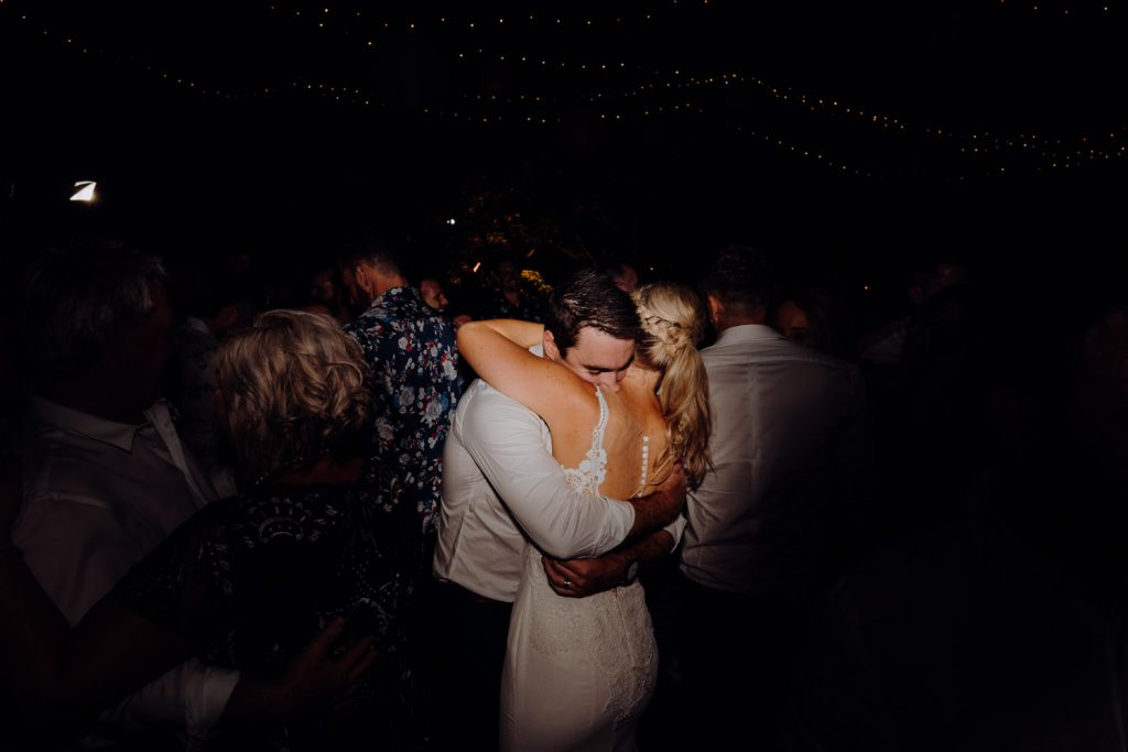 bride and groom dancing close on the their wedding day in Broome with friends and family around them