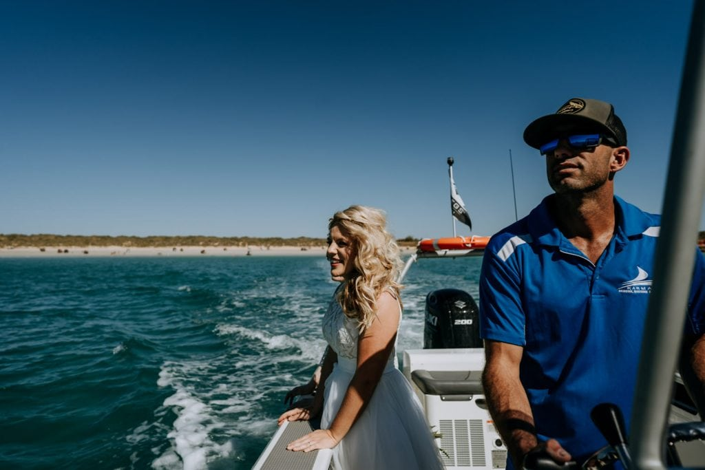 bride on small vessel looking out toward Broome catamaran with Cable Beach in the distance