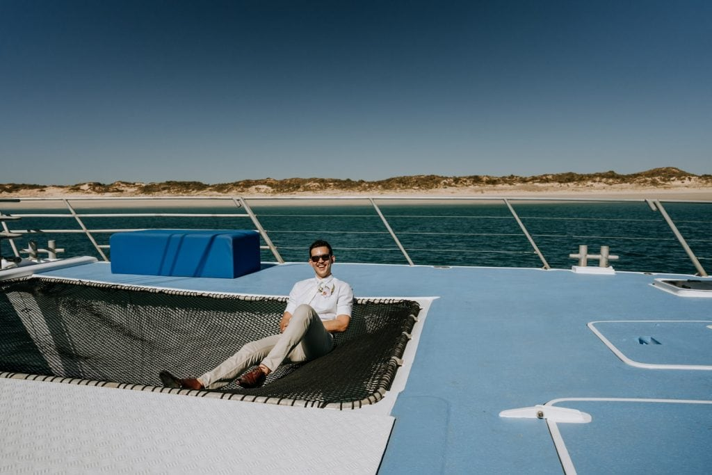 young groom wearing sunglasses sitting on a large net on sailing Broome catamaran