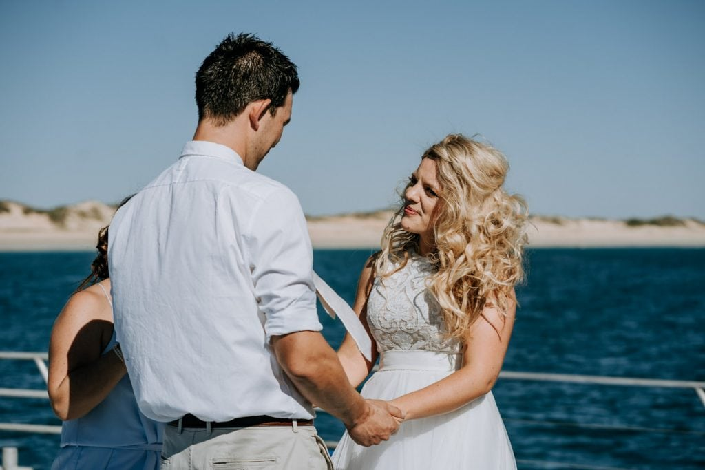 bride and groom stand opposite each other during their wedding ceremony on Broome catamaran