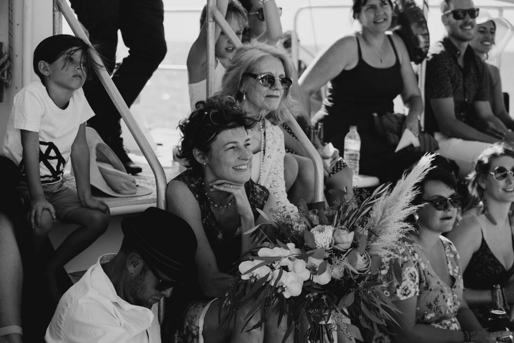 wedding guests and mother of the bride watch wedding ceremony on Broome catamaran Karma IV