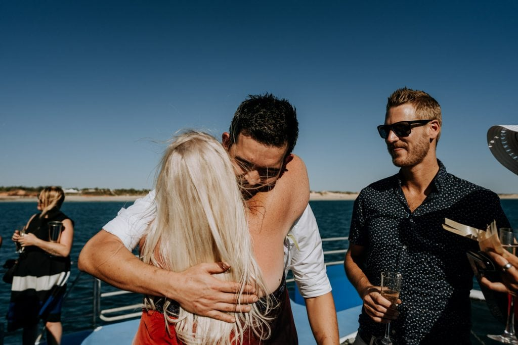 woman in red dress and blonde hair congratulates groom on Broome catamaran