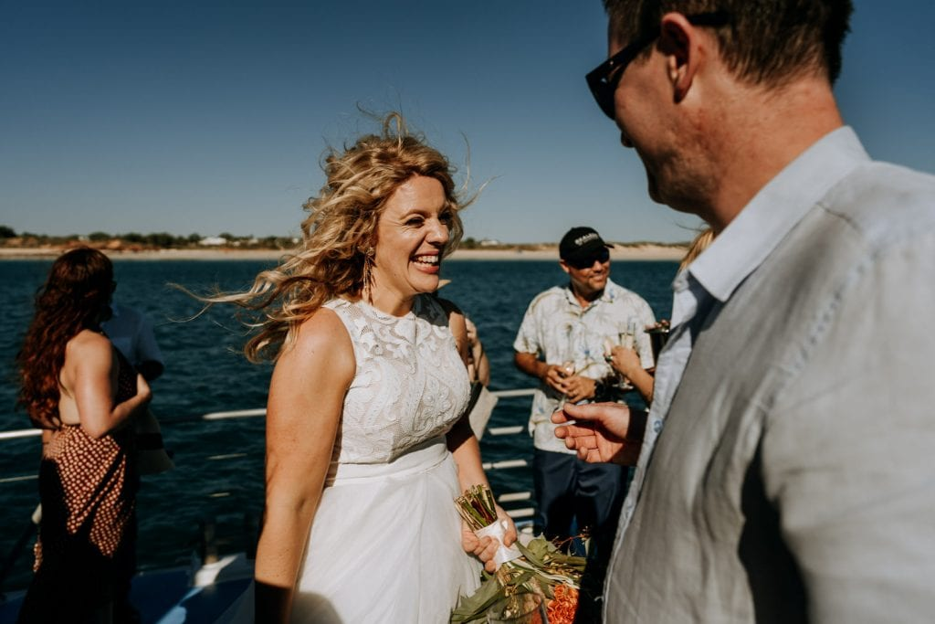 smiling bride looking happy at her wedding on a boat off the coast of Broome in Western Australia