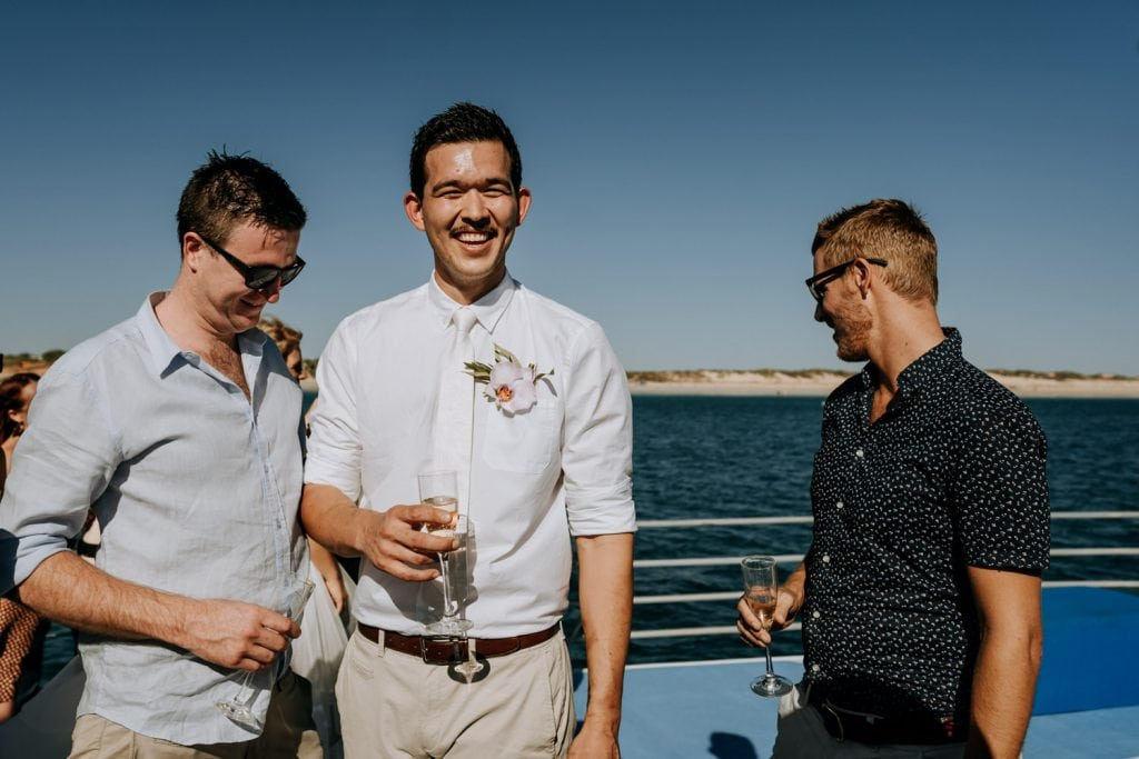 Three young man drinking champagne on sailing yacht in Broome