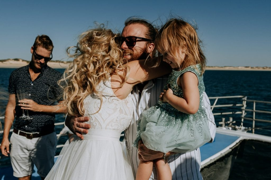 woman in white wedding dress hugs wedding guests on Karma IV Broome catamaran vessel