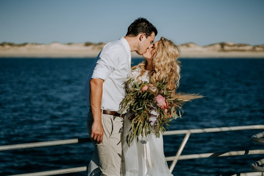 wedding couple kissing on deck of Broome catamaran after their wedding ceremony