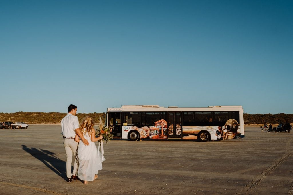 wedding couple walking towards Broome Explorer bus parked on Cable Beach