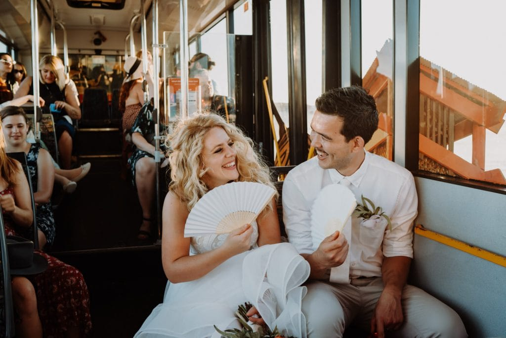 bride and groom and their wedding guests travel on Broome Explorer Bus after catamaran wedding