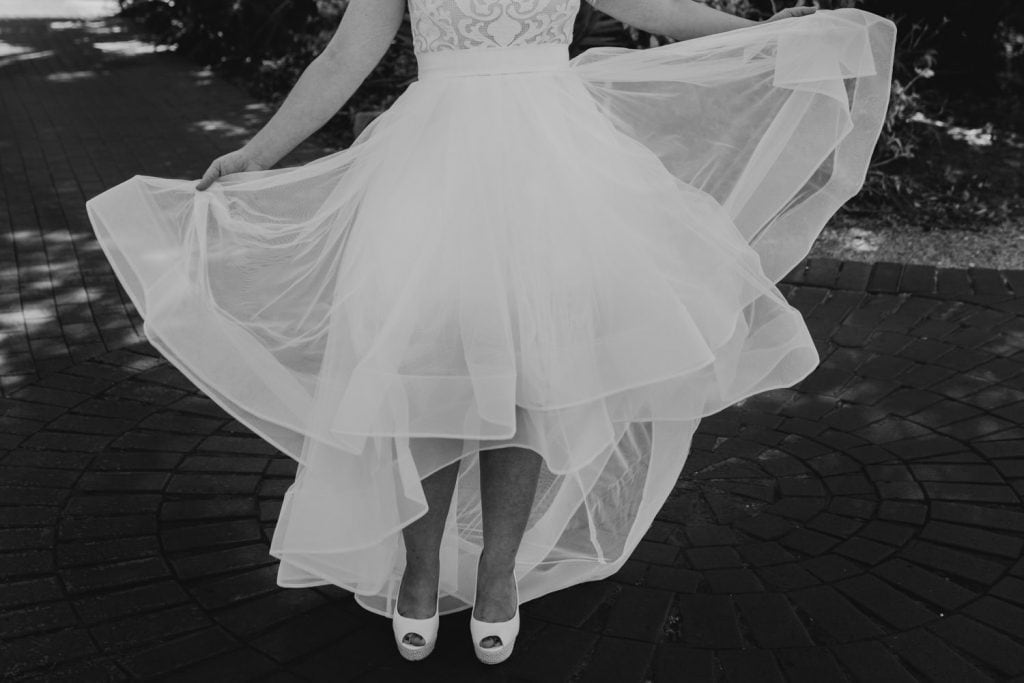 black and white photo of woman's legs in white heels and wedding dress