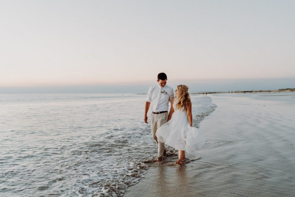 young wedding couple walking along Cable Beach after sunset holding hands