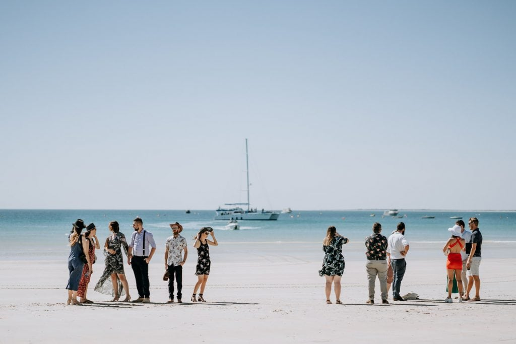 group of people standing on Cable Beach with Broome catamaran Karma IV in the backgroun