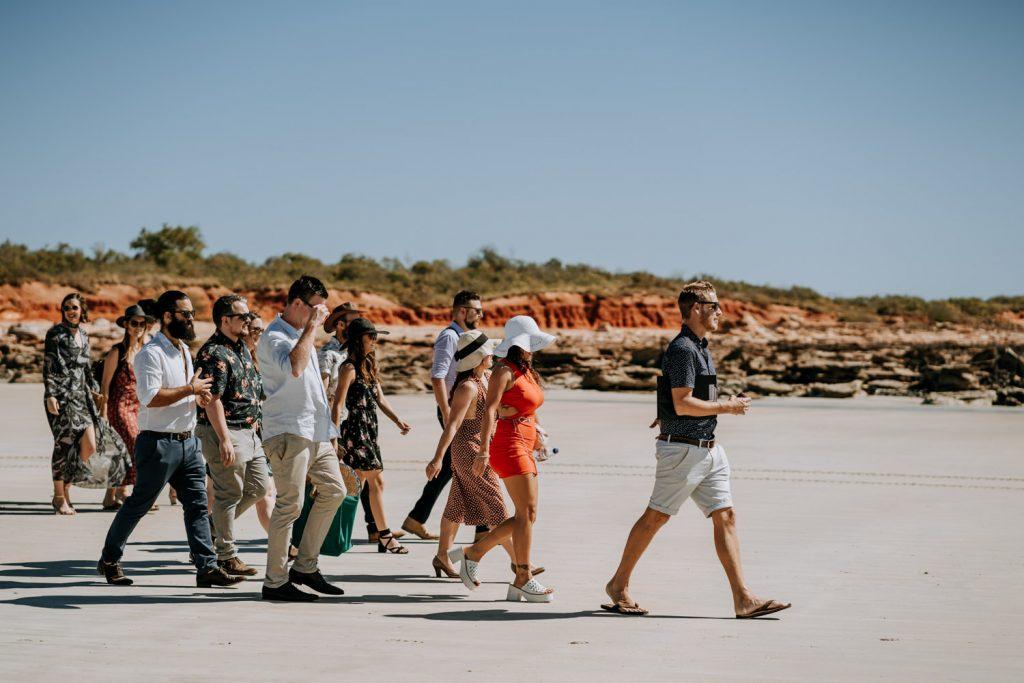 wedding guests in summery clothes walk towards Broome catamaran