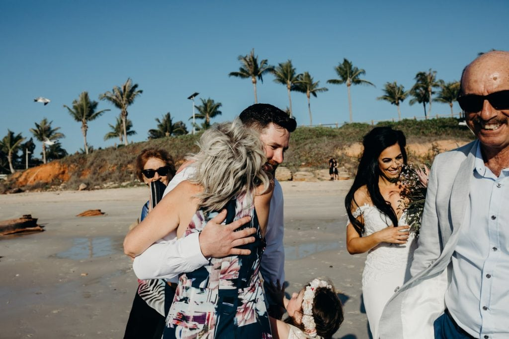 woman is congratulating groom at his beach wedding with a big hug