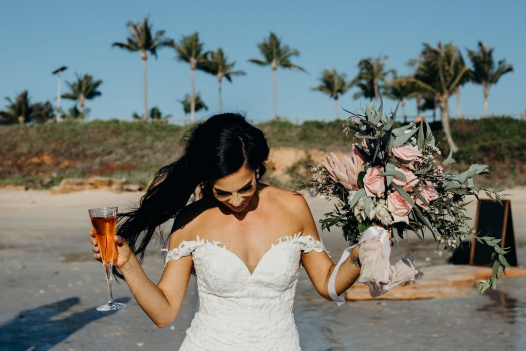 bride in wedding dress and with a glass of champagne in her hand at her Cable Beach Wedding in Broome