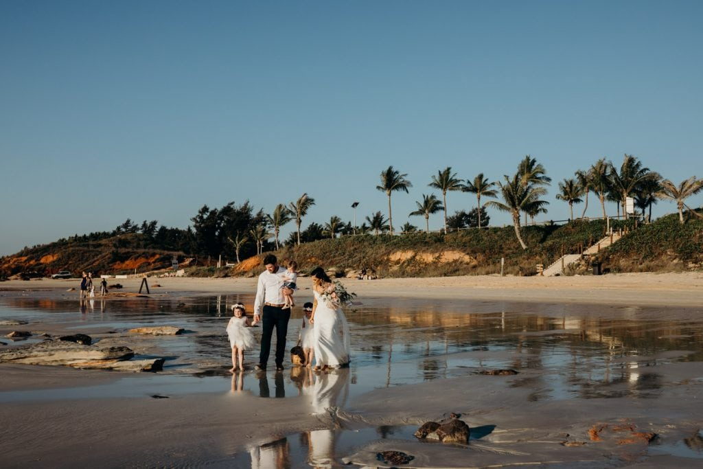 bride and groom with their three small children walking along Cable Beach