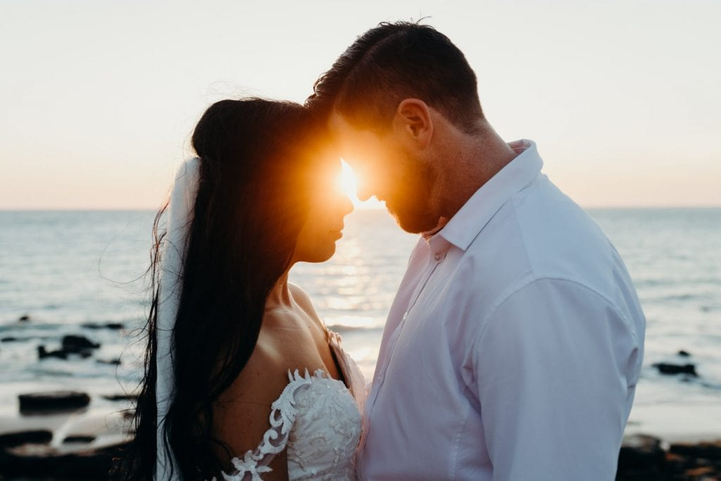 sunset photo of a wedding couple with the sun beams poking in between them
