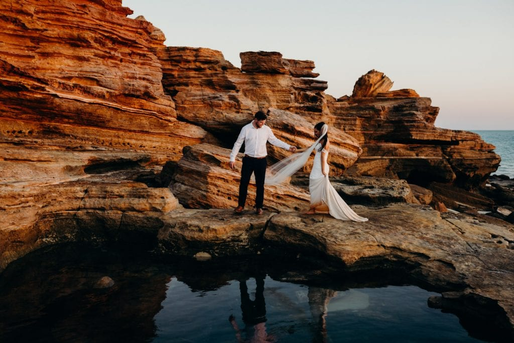bride holding the hand of her groom among the red cliffs at Gantheaume Point in Broome