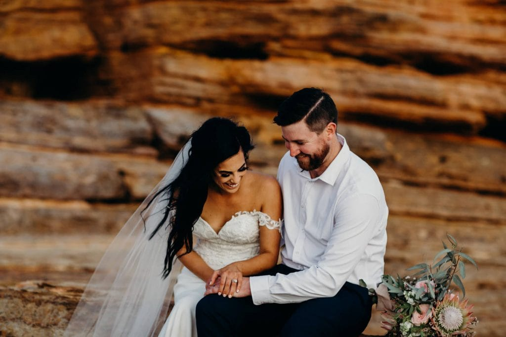 wedding couple in Broome sitting on a rock smiling and laughing
