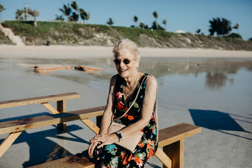 older woman sitting on a bench seat at Cable Beach wedding